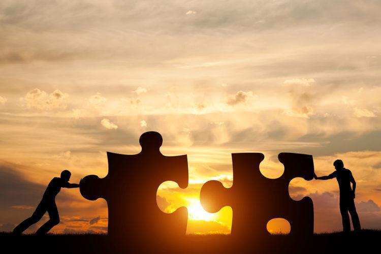 Двое мужчин соединяют две части головоломки. Закатное небо. Концепция бизнес-решения, работа в команде, решение проблемы, вызов